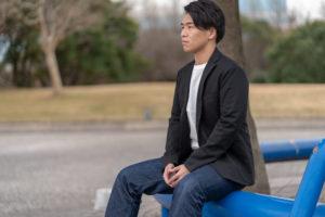 屋外のベンチに座る男性