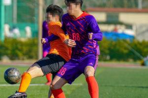 サッカーの試合で競り合う2人