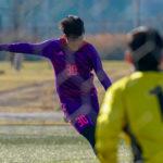 サッカーの試合でシュートを打つ瞬間の男性